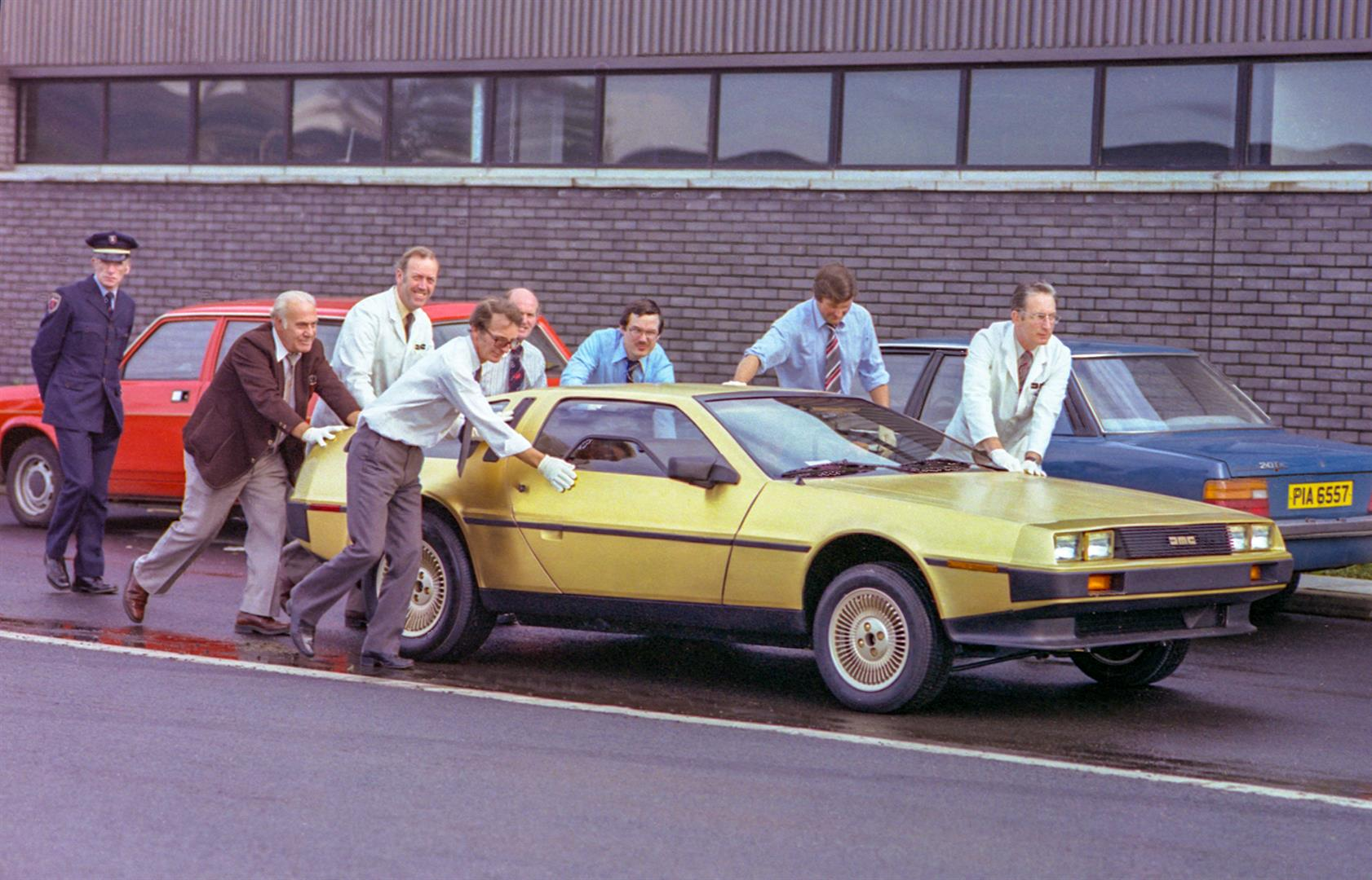 Moving the Gold car, with Tony McDade at rear and Dick Kendall second from the left | DeLoreanDirectory.com